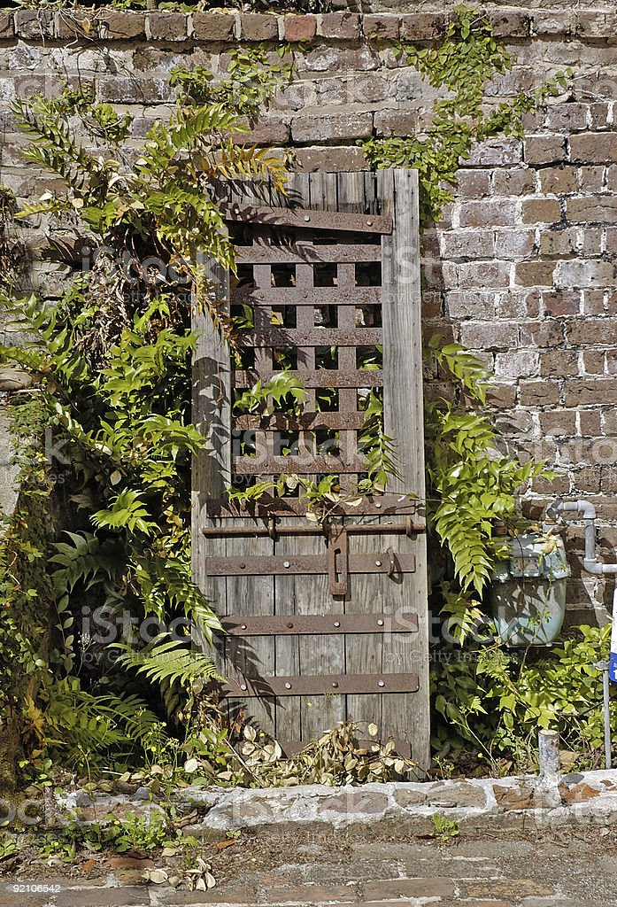 old rusty door propped on brick wall royalty-free stock photo