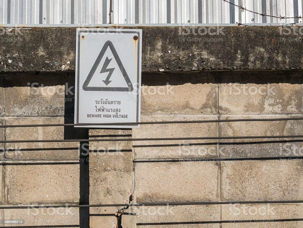 Old rusty electricity shock caution sign on the aged wall. royalty-free stock photo
