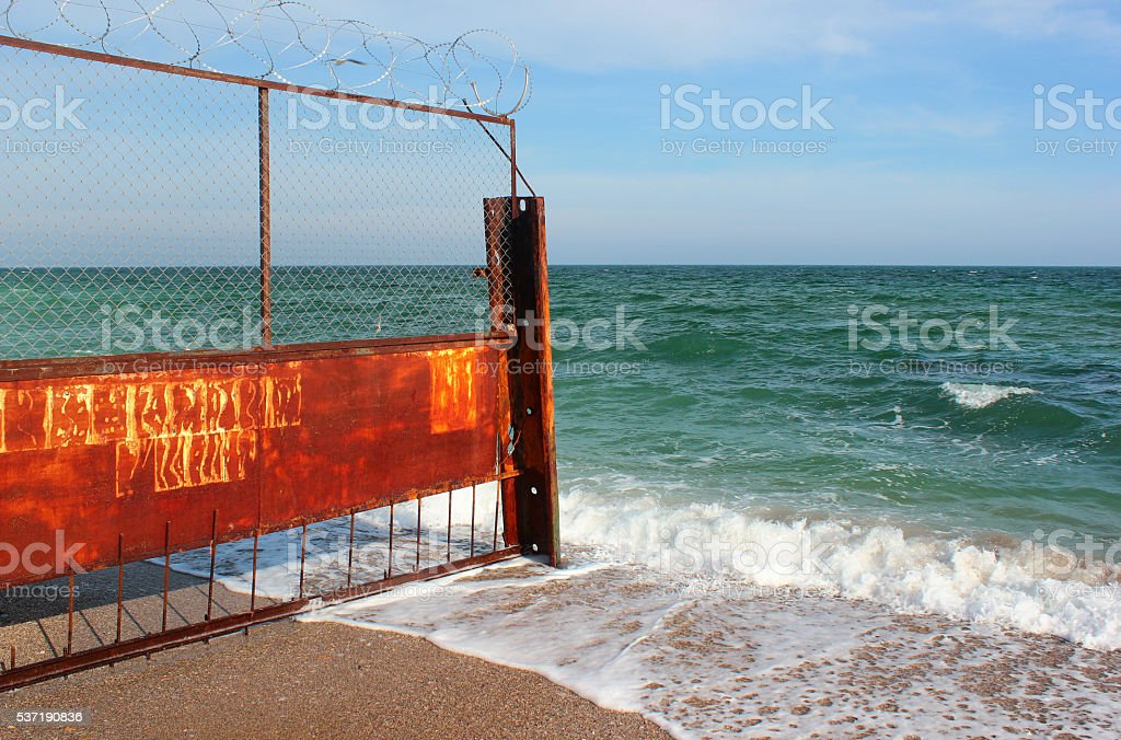 Old rusty fence on seashore. Restricted area on a beach stock photo