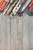 old rusty hand tools and instrument on wooden plank background