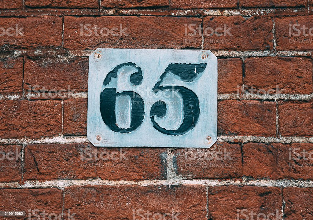 Old rusty house number 65, on plate on bricks stock photo