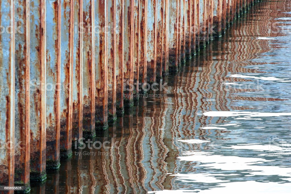 Old rusty iron pier reflected in water stock photo