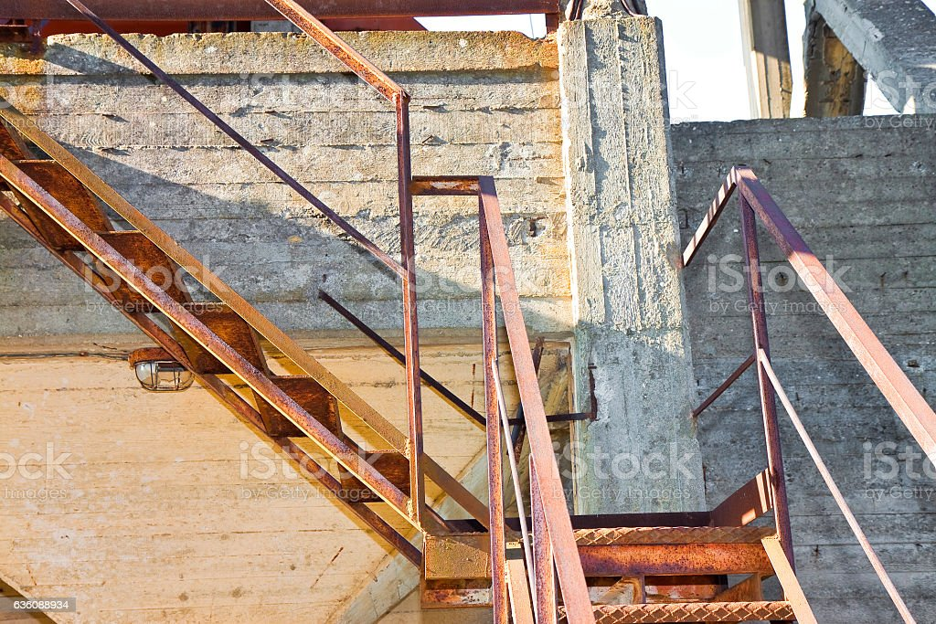 Old rusty iron staircase against a damaged concrete wall stock photo