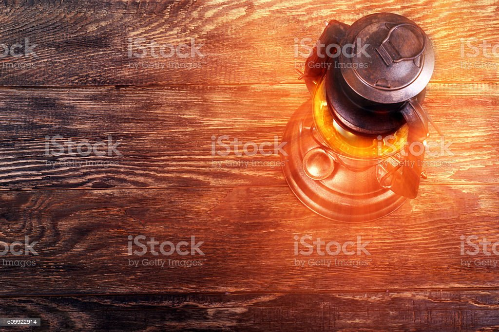 Old rusty kerosene lantern on wooden floor stock photo