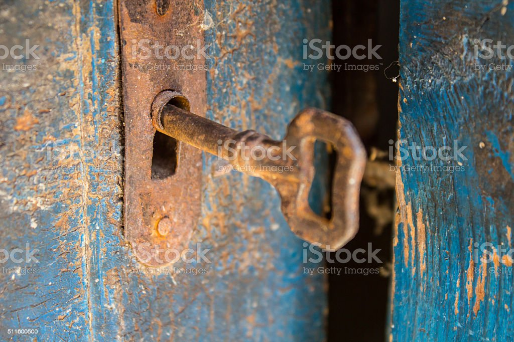 Old rusty key and keyhole on a blue wooden door stock photo