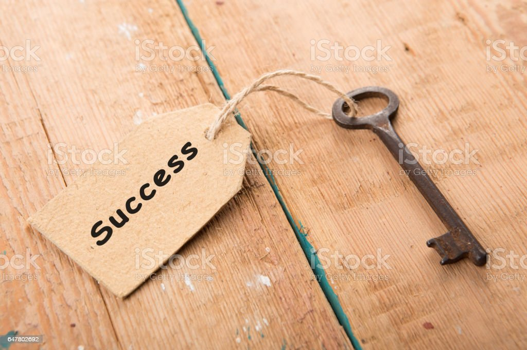 Old rusty key with a paper label - Success stock photo
