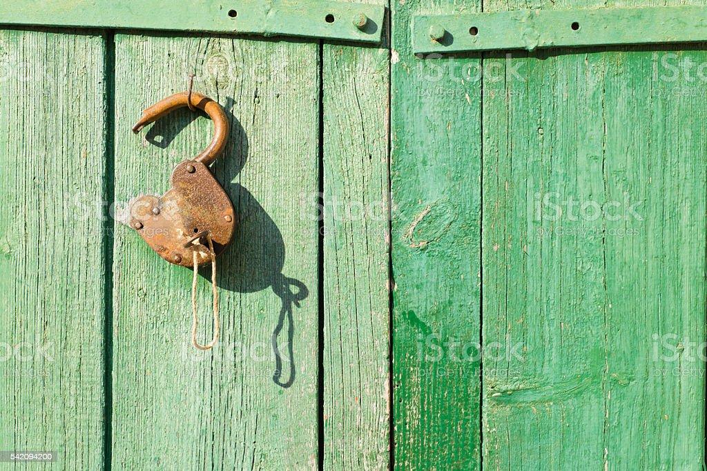 old rusty lock on a wooden door stock photo