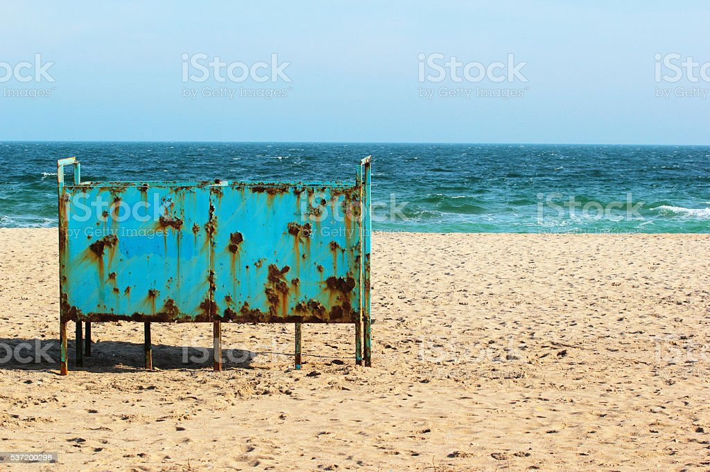 Old rusty metal cabana on empty sandy beach stock photo