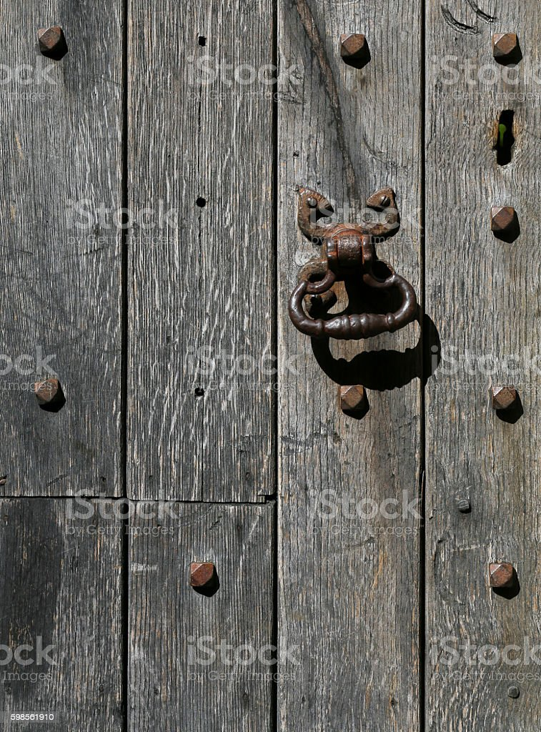 Old rusty metal door knocker on a aged oak timber stock photo