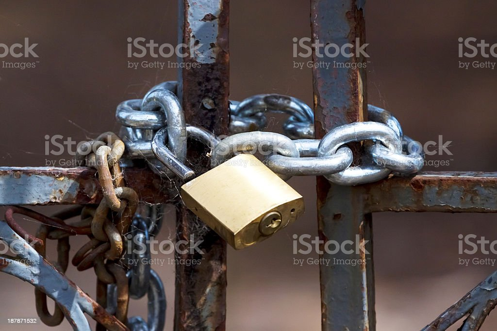 Old rusty metal gate with padlock and chain stock photo