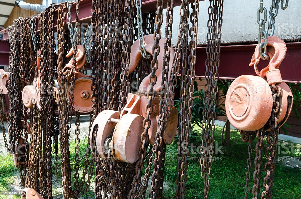 Old rusty metal hoist chain and pulley stock photo