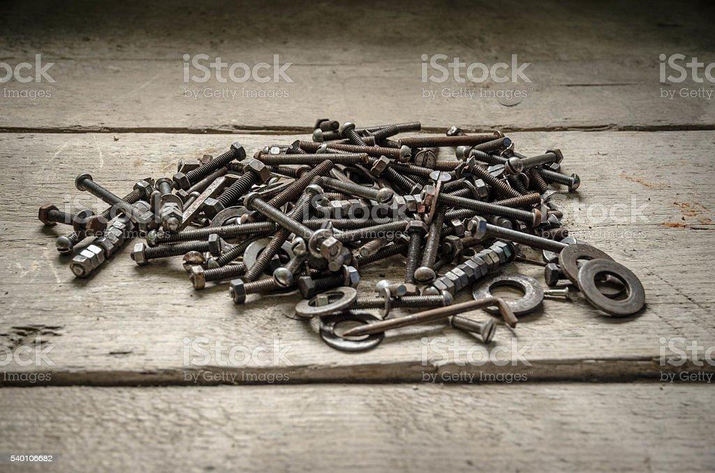 Old rusty metal screws on an hardwood workbench stock photo