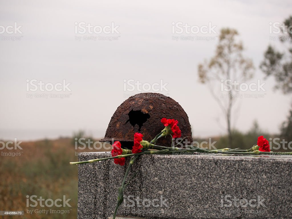 Old rusty military helmet with big hole lies at memorial stock photo