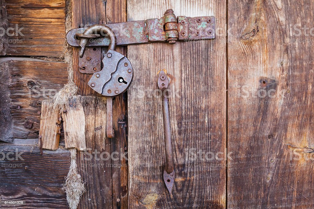 Old rusty padlock and latch on a wooden door stock photo