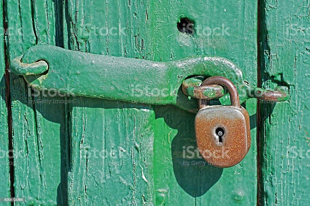 Old Rusty Padlock on Green Wooden Door stock photo