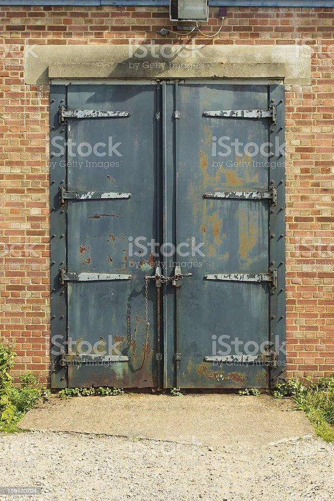 Old rusty padlocked blue metal door royalty-free stock photo