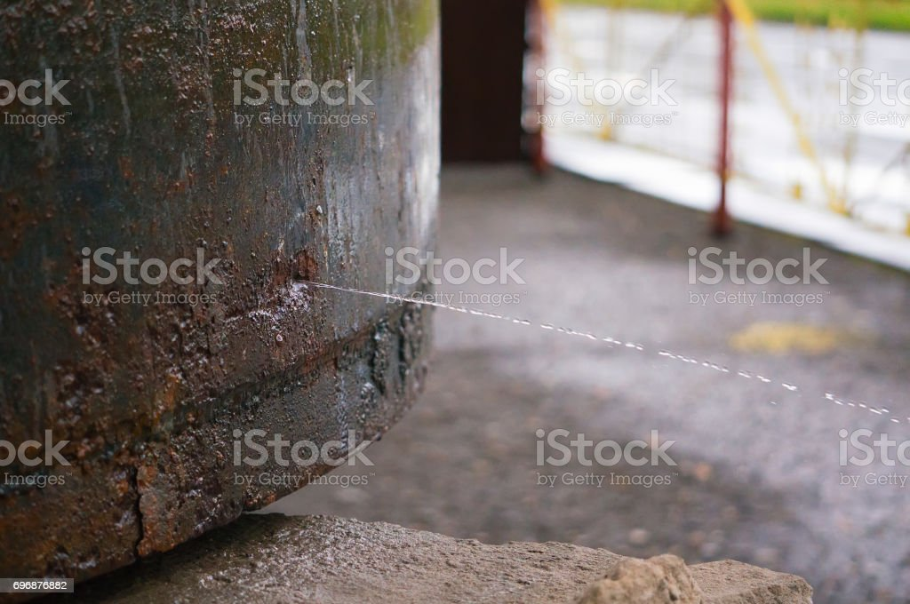 Old rusty pipe with leak and water spraying out stock photo