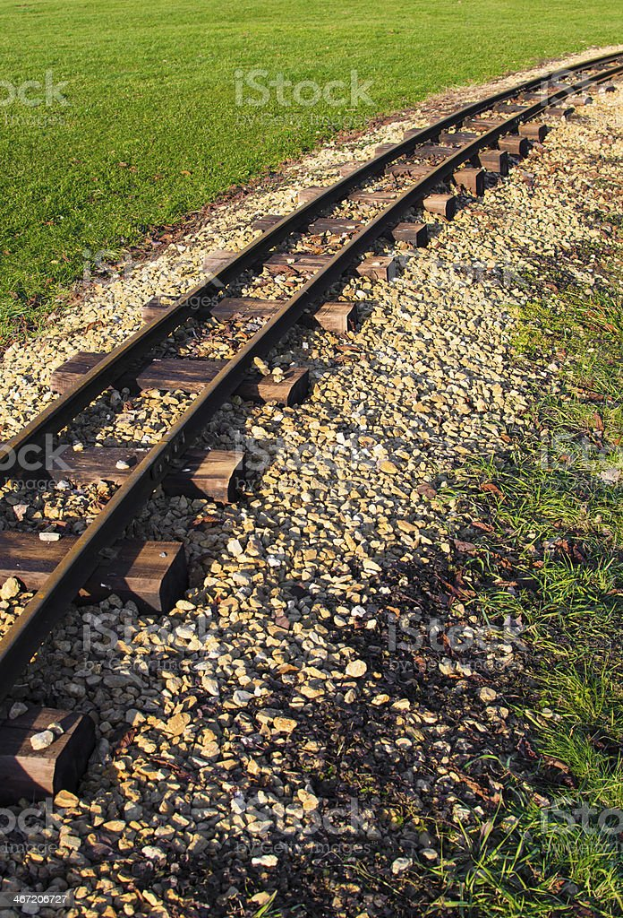 old rusty railtracks through a meadow stock photo