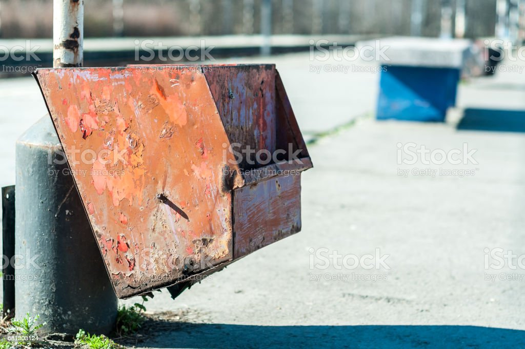 Old rusty red street garbage can. Garbage in the city. Litter. stock photo