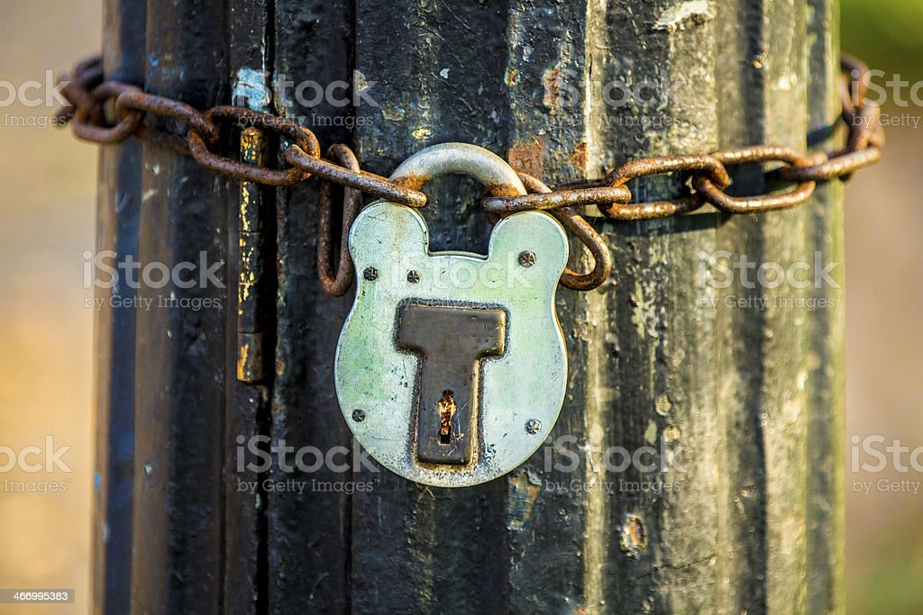 Old rusty reliable Padlock chained to post royalty-free stock photo