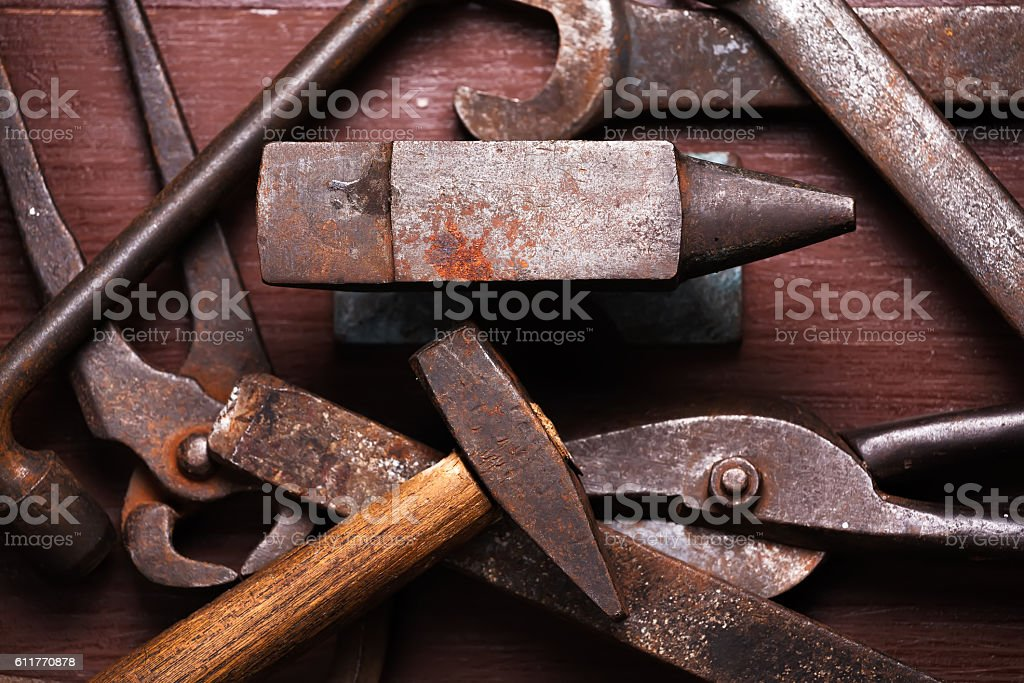 Old rusty rugged anvil and other blacksmith tools. stock photo