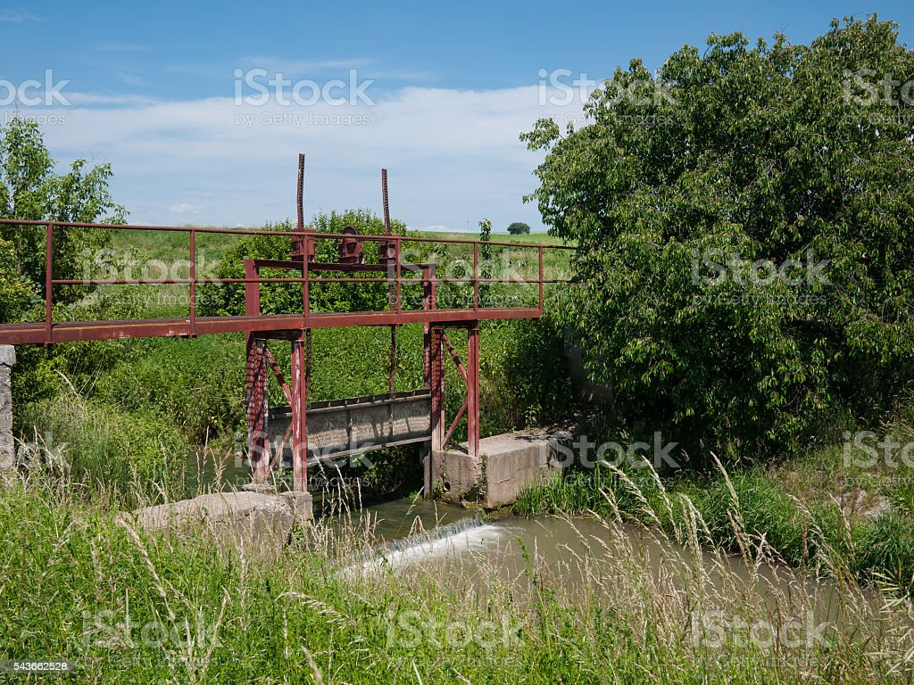 Old rusty sluice on the river stock photo