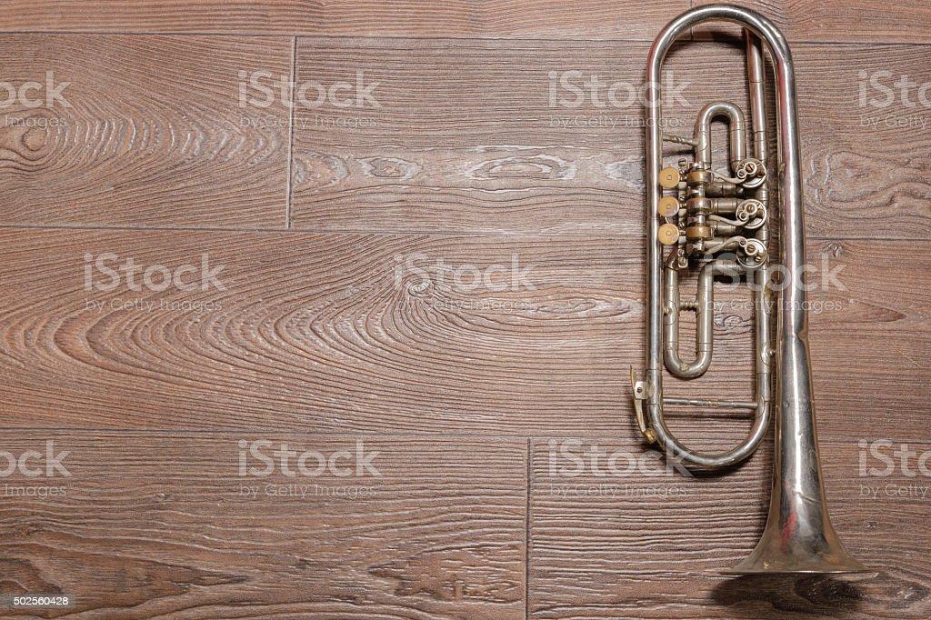 Old rusty trumpet lays on wooden floor stock photo