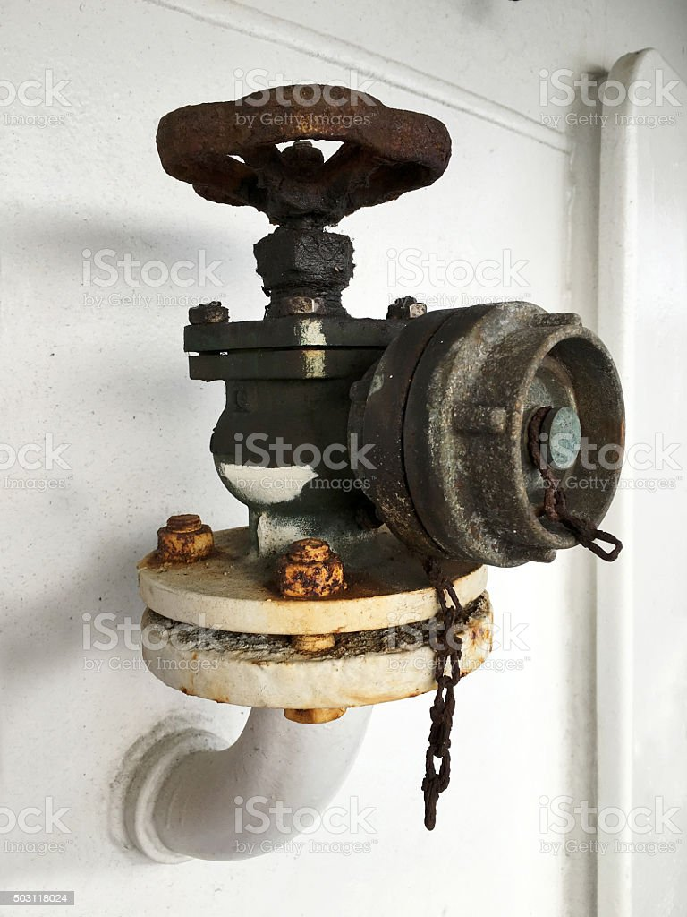 Old rusty valve on white wall. stock photo