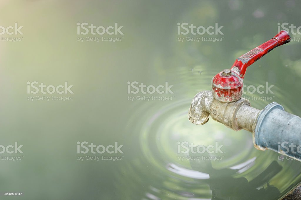 Old rusty water tap with drop on pond. stock photo