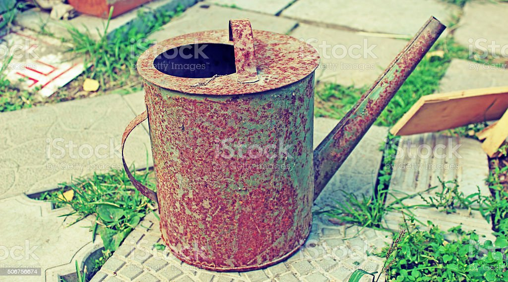 Old rusty watering can in the garden stock photo