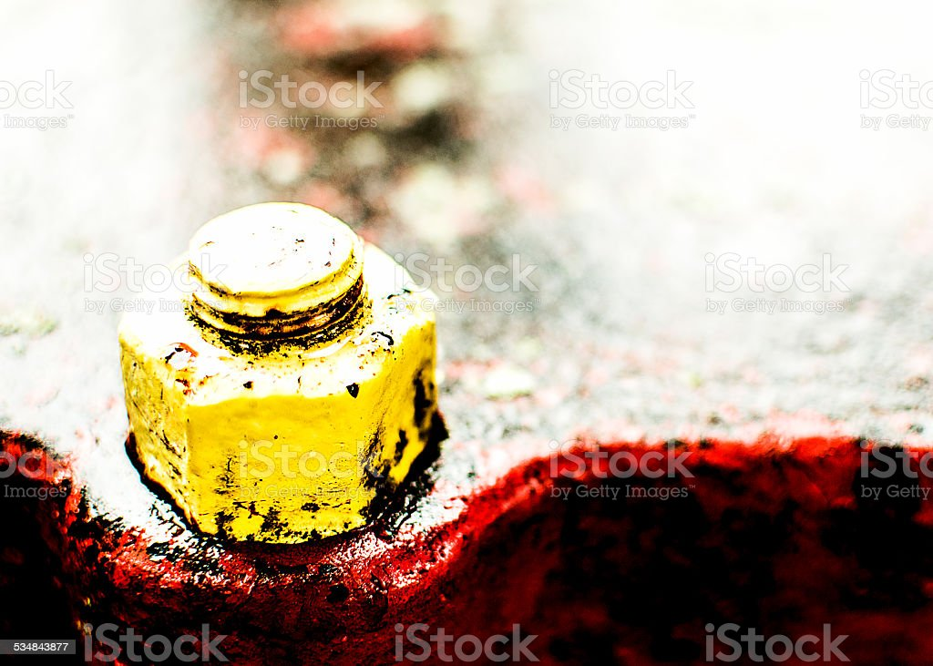 Old Rusty Yellow Bolt with Red Metallic Background royalty-free stock photo