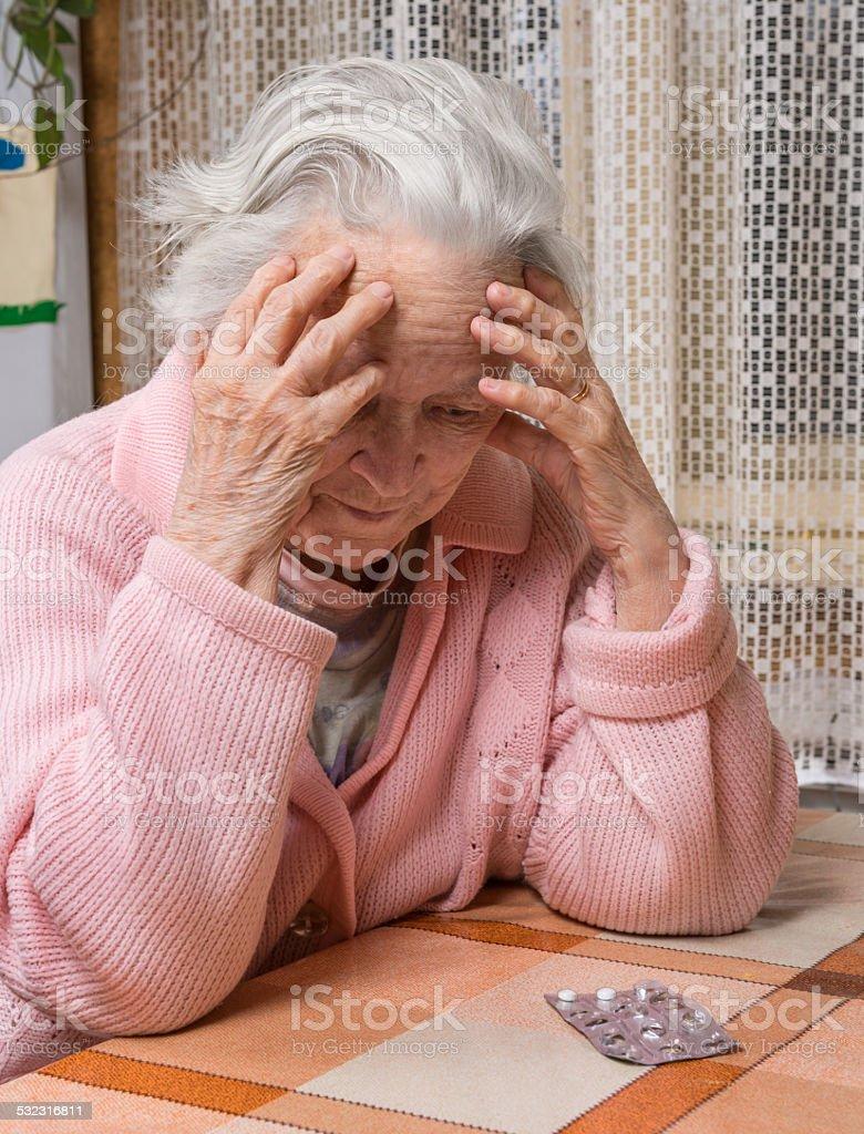 Old sad woman holding pills stock photo