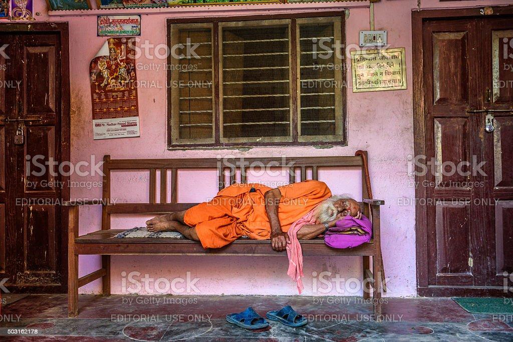 Old sadhu baba sleeping on a bench in Nepal stock photo