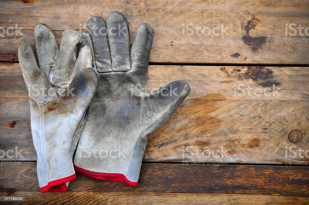 Old safety gloves on wooden background, Gloves on dirty works. stock photo