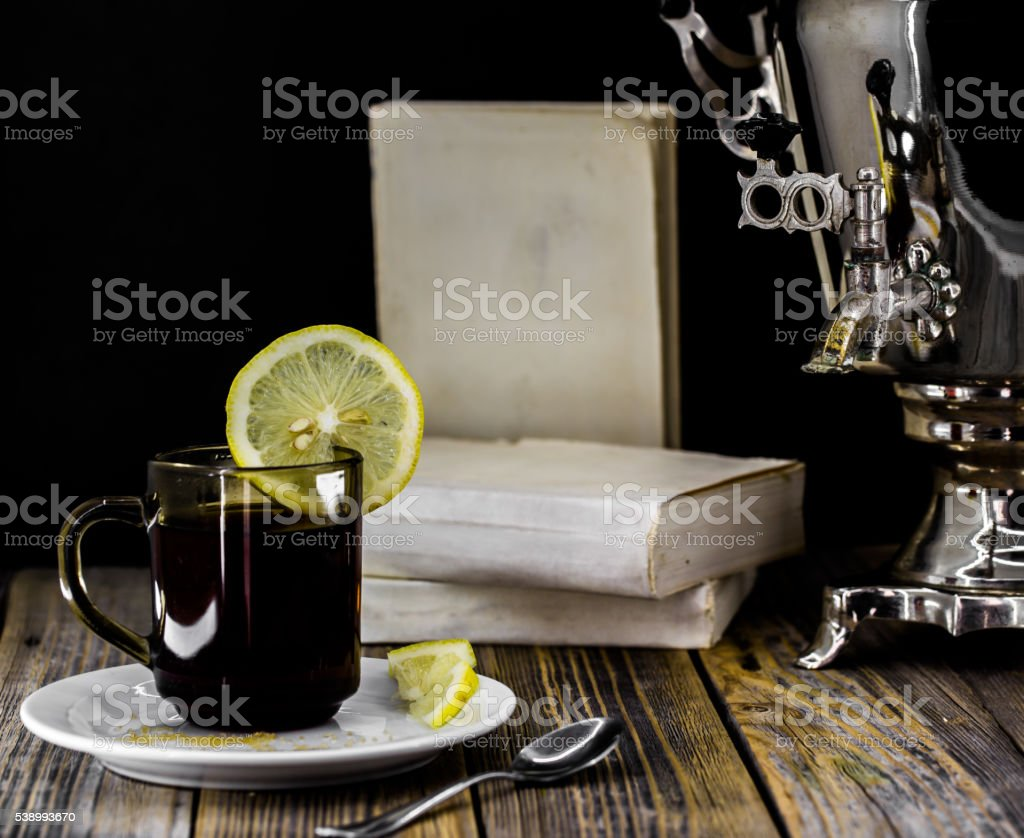 old samovar and tea Cup with lemon on wooden background stock photo