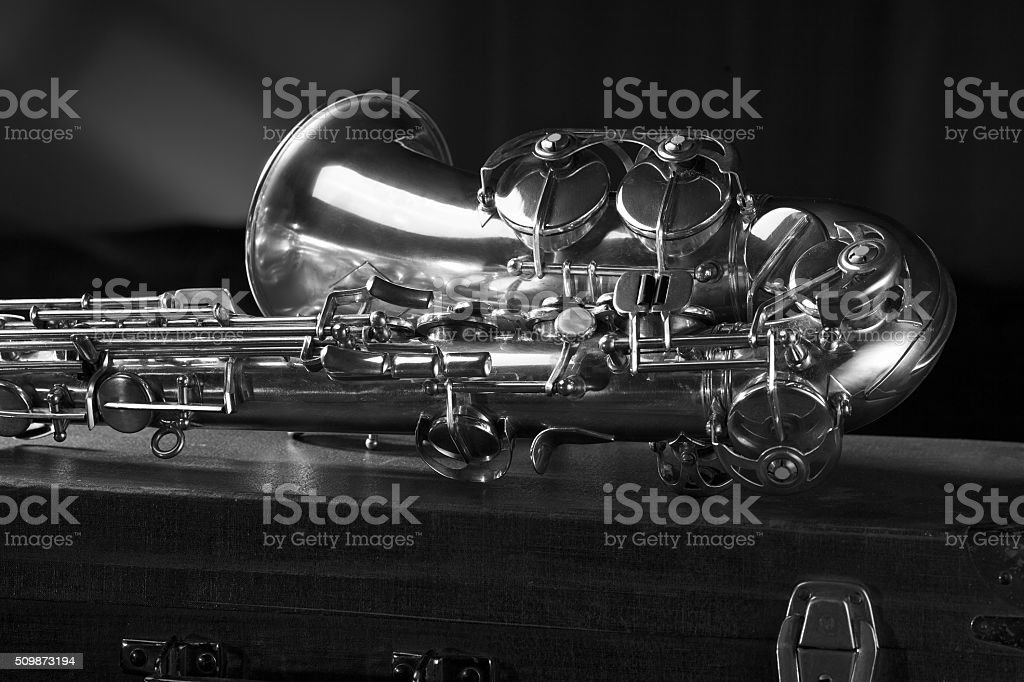 Old saxophone lying on the suitcase. stock photo