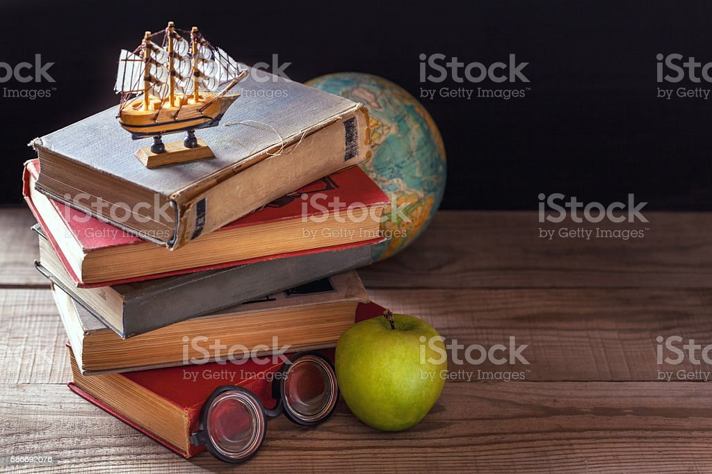 Old school books and  supplies lie on a wooden table. stock photo