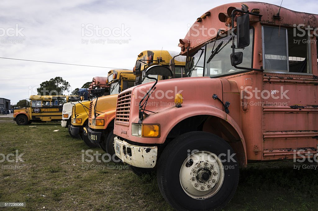 Old School buses parked alongside a road in Immokalee, Florida. stock photo