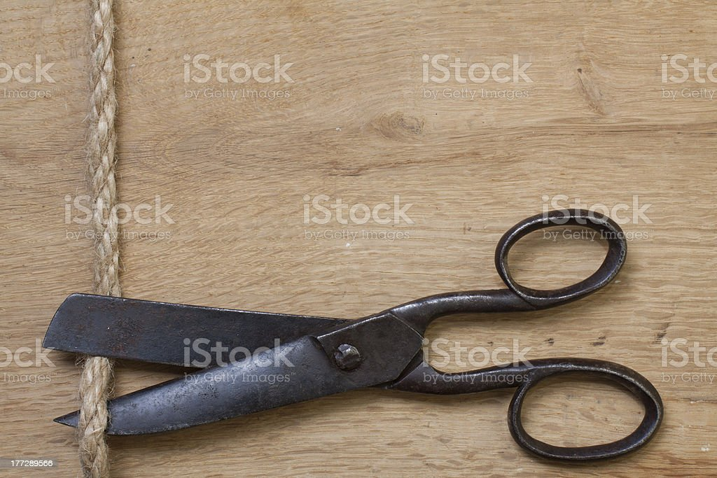 Old scissors on wood cutting rope royalty-free stock photo