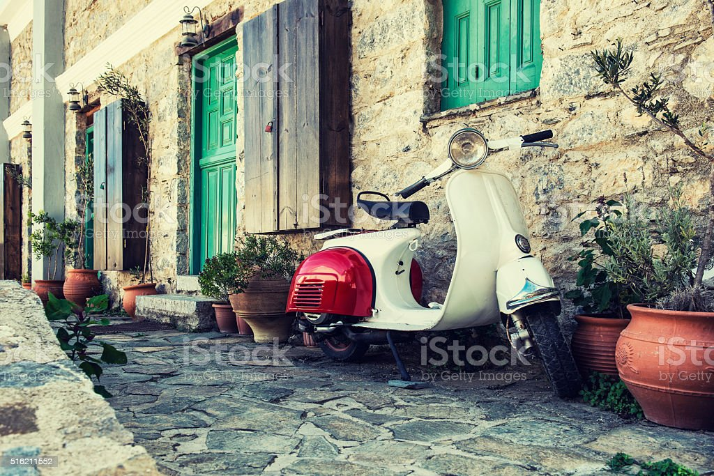 Old scooter parked by the wall stock photo