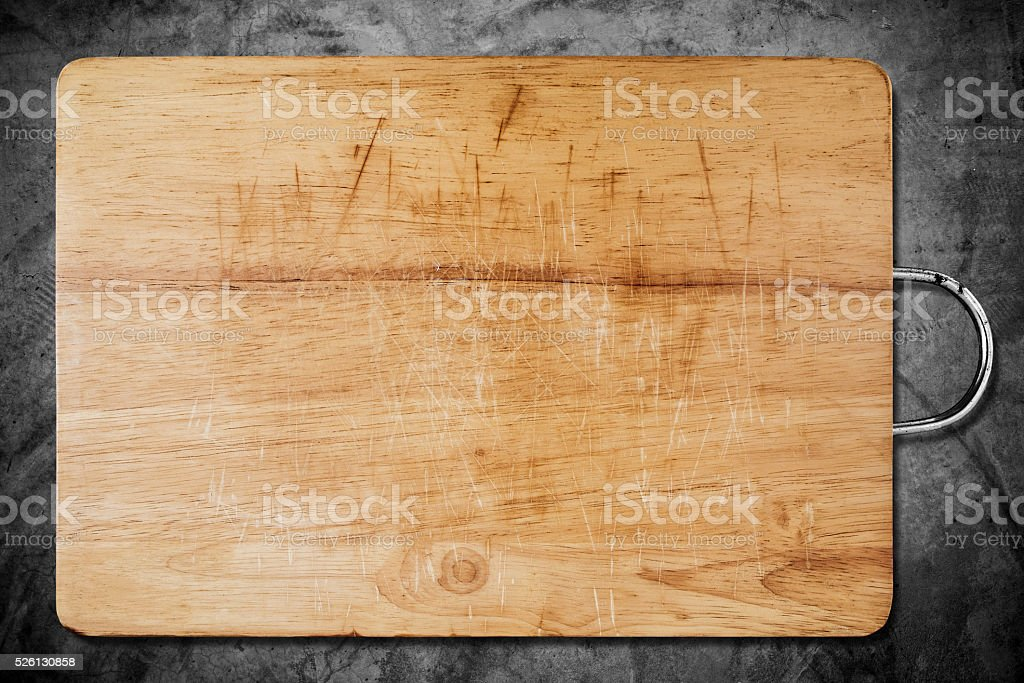 Old scratched wooden cutting board, on dark concrete texture stock photo