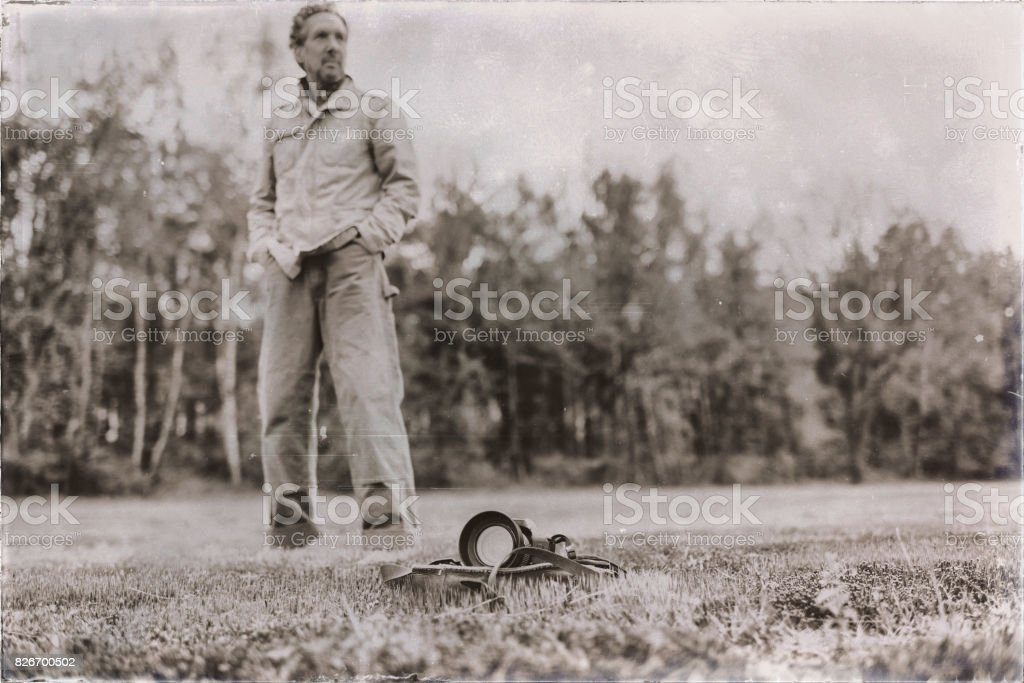 Old sepia photo of man standing behind leather bag with camera lying in field. stock photo