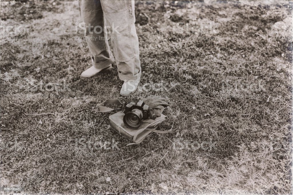 Old sepia photo of man standing next to leather bag with gloves and camera lying in field. High angle view. stock photo