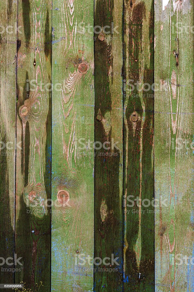 Old shabby wooden fence background with a trace of ads. stock photo