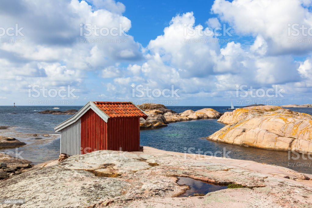 Old Shed at the rocky beach by the sea stock photo