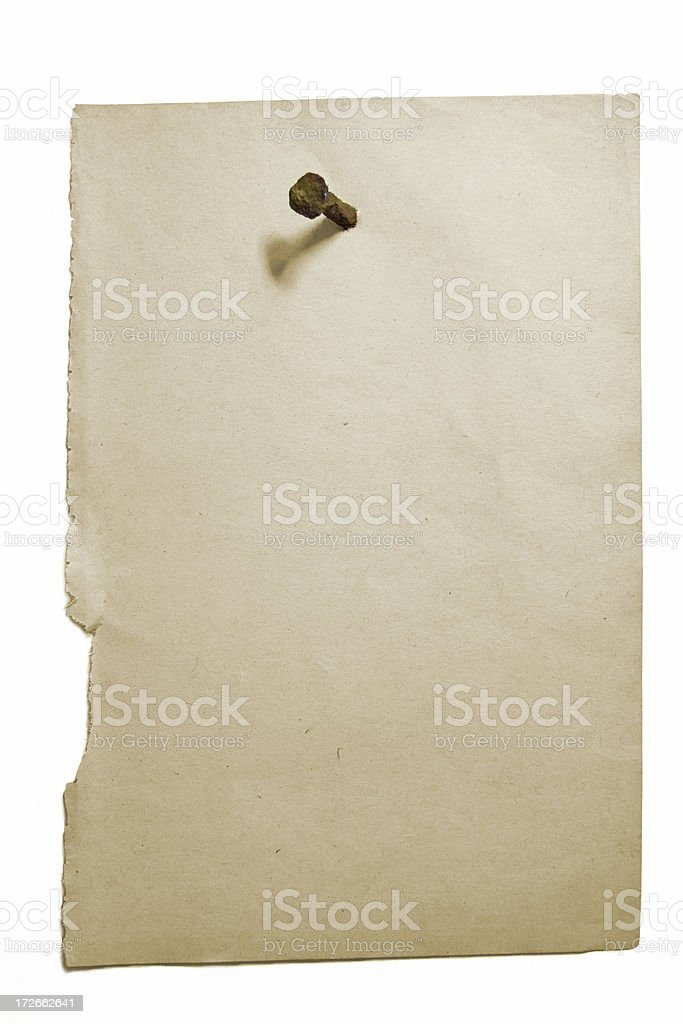 Old sheet of paper on a white background nailed. stock photo