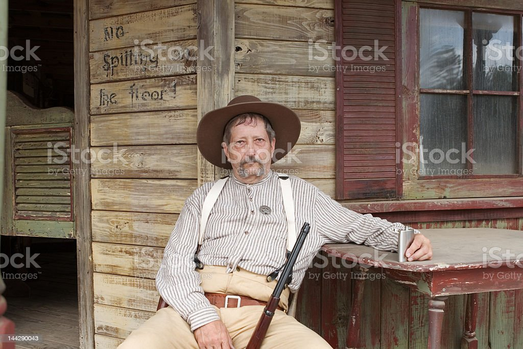 Old Sheriff Cowboy Rifle Sitting Outside Weathered Saloon with Flask royalty-free stock photo