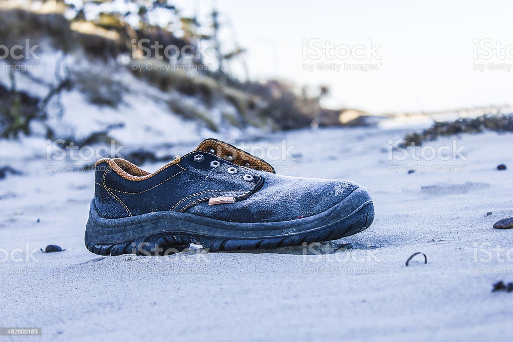 Old shoe on the shore stock photo