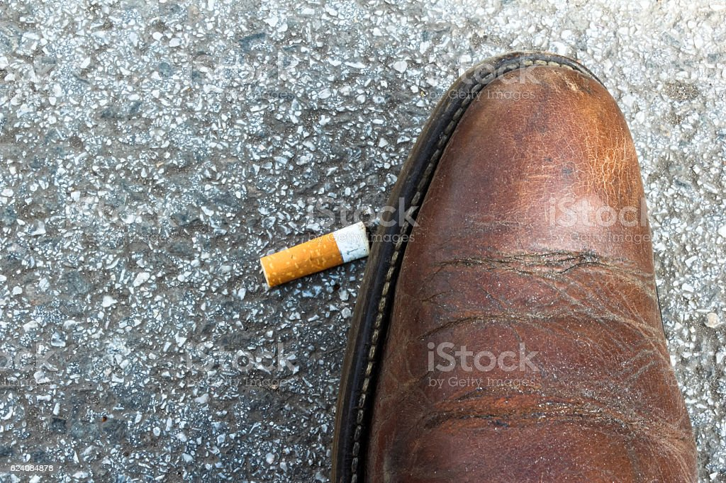 Old shoe trampled cigarette butt stock photo
