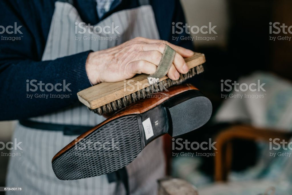 Old shoemaker is polishing a shoe stock photo